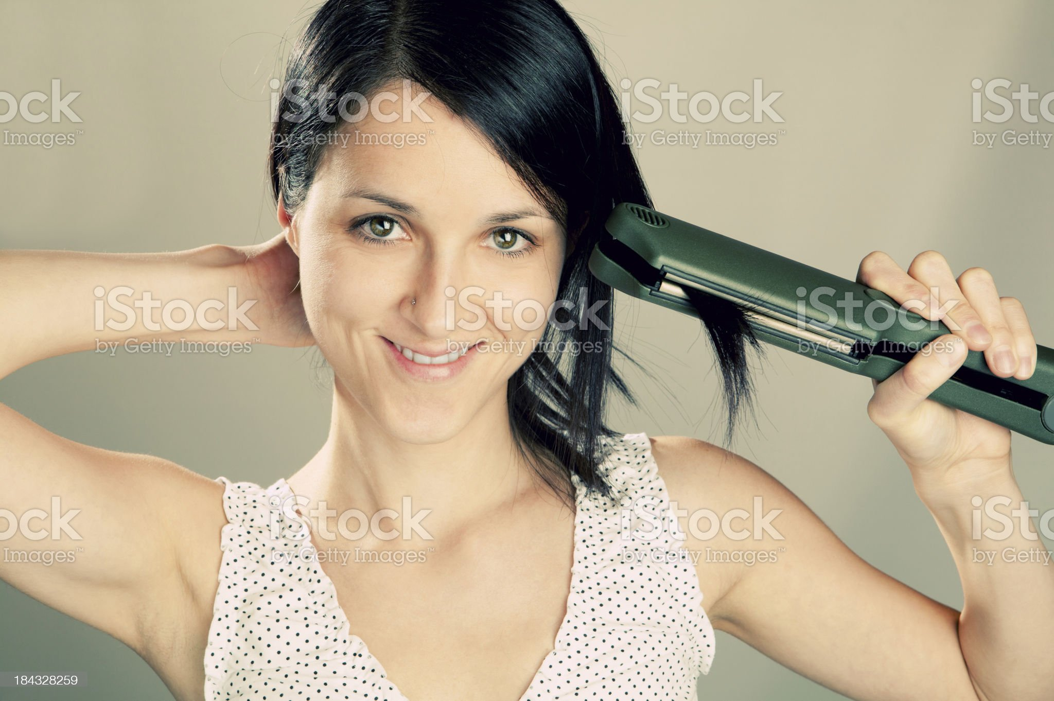 Girl using hair straightener royalty-free stock photo