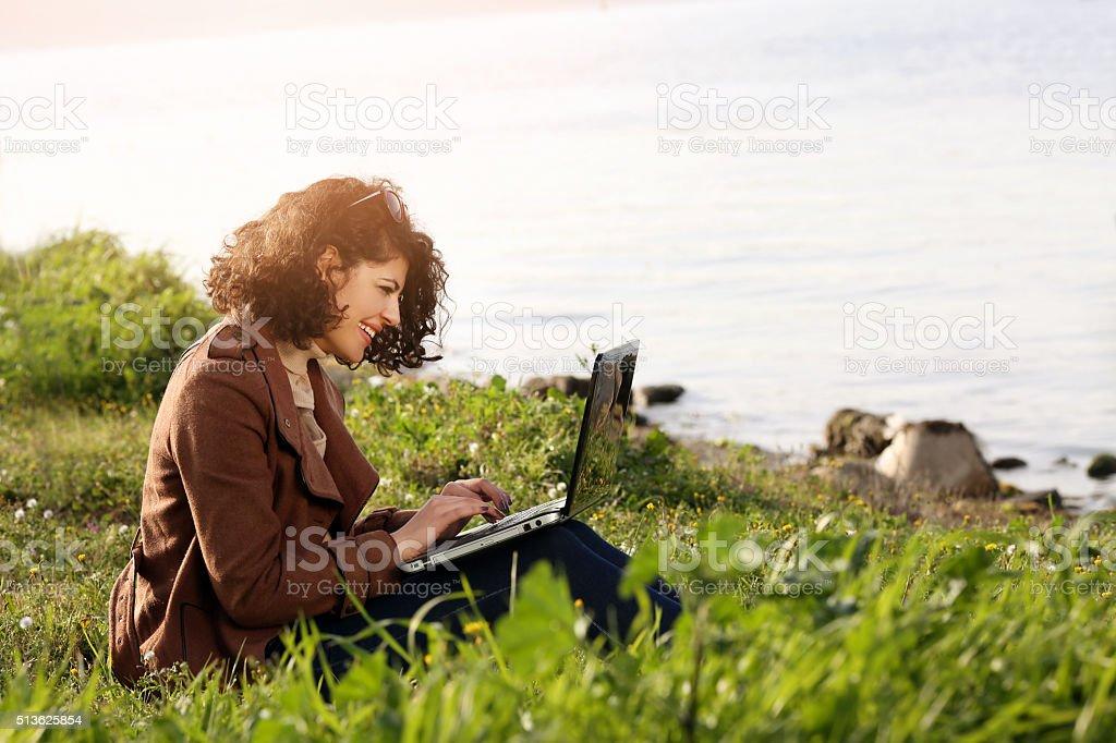 Girl using lap top among nature stock photo