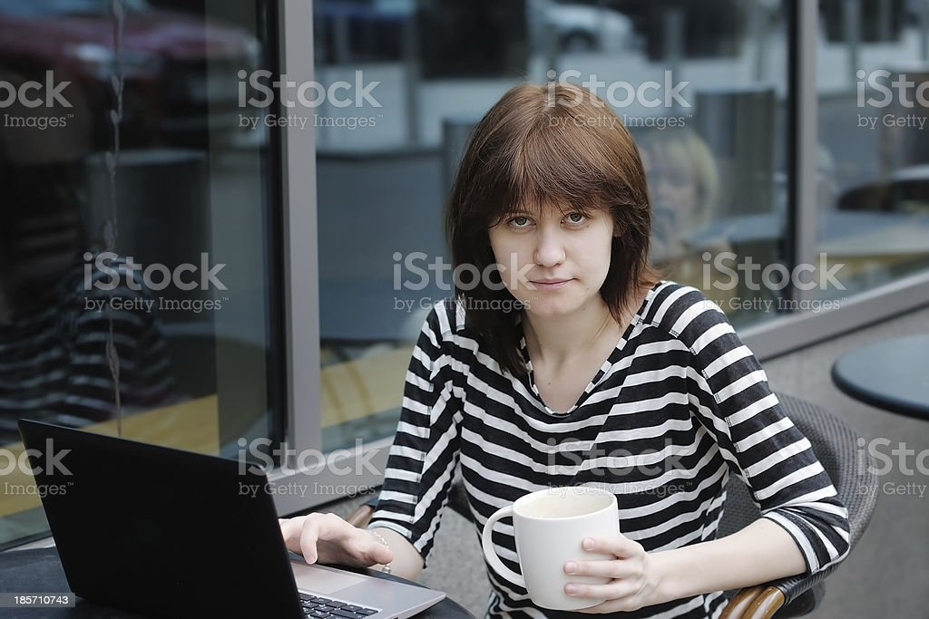 Girl using laptop in a outdoor cafe royalty-free stock photo