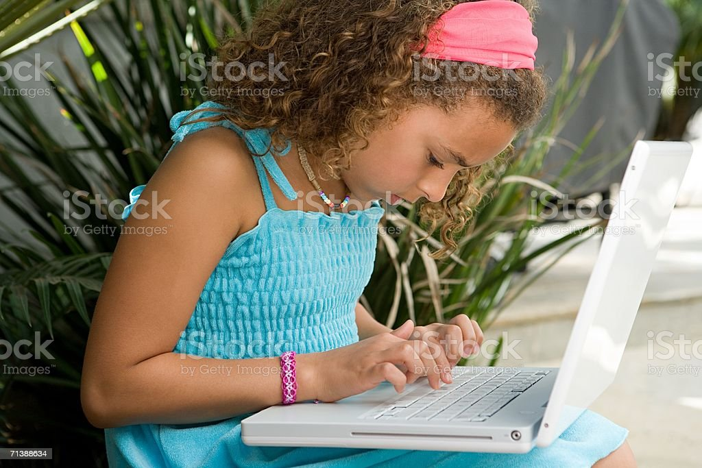 Girl using laptop outdoors stock photo