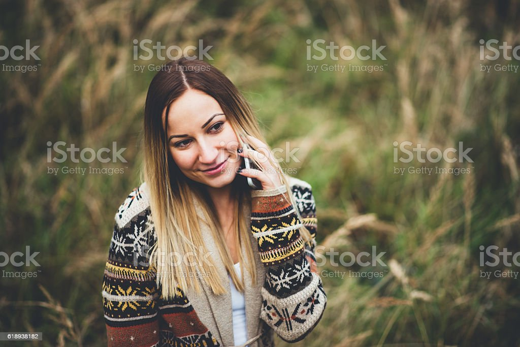 girl using phone in field stock photo