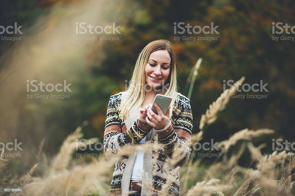 girl using phone in field stock photo