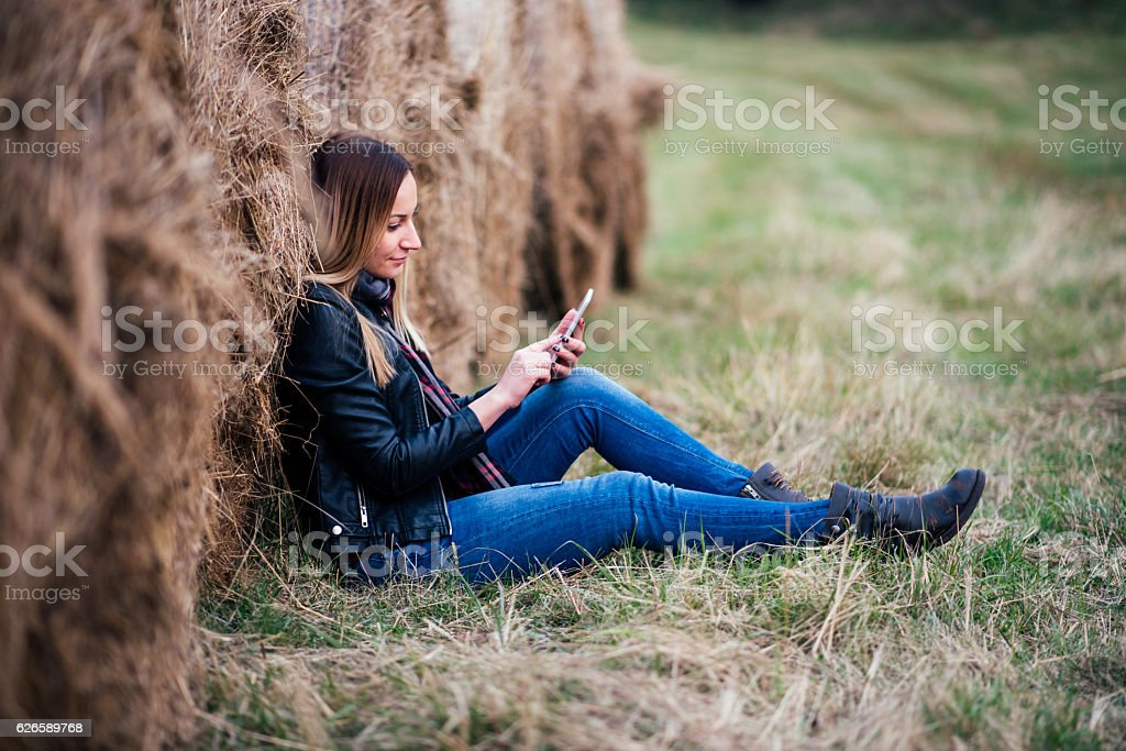 girl using phone in the field stock photo