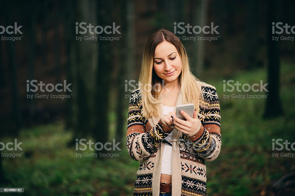 girl using phone in the forest stock photo