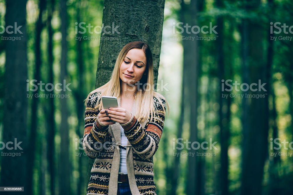 girl using phone in the nature stock photo