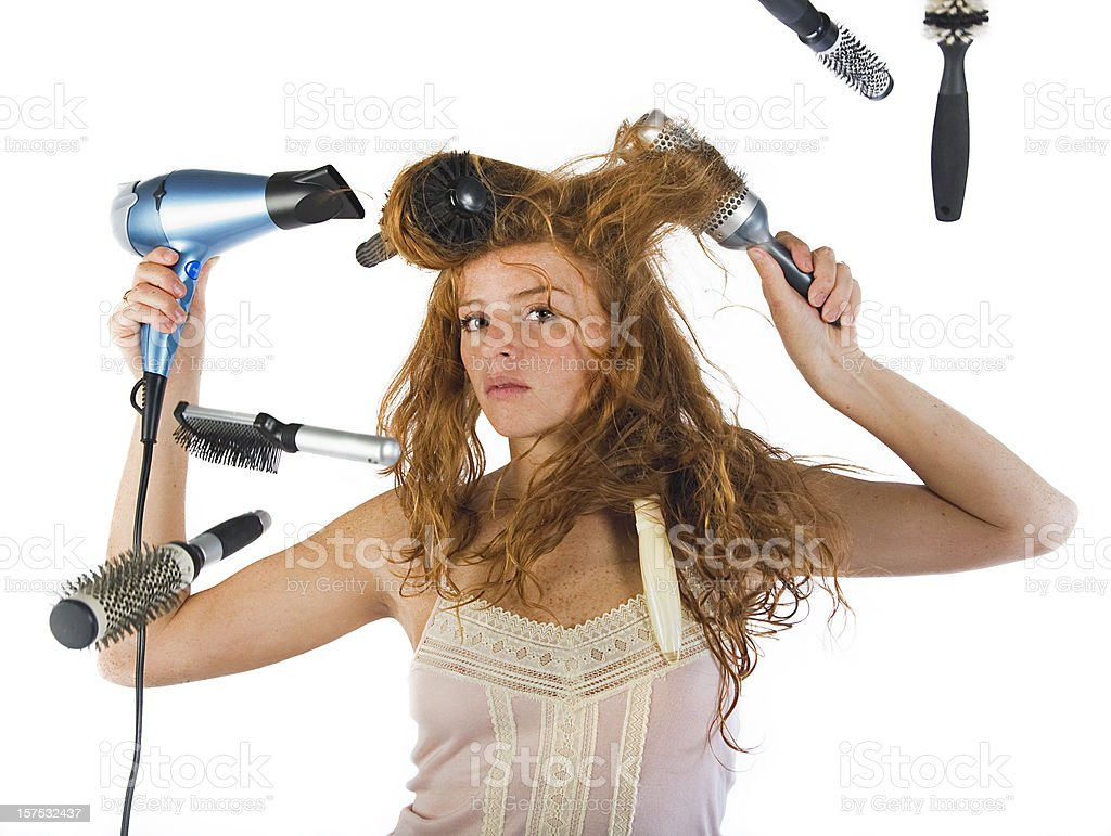 Girl using six brushes and a hair dryer to style her hair stock photo
