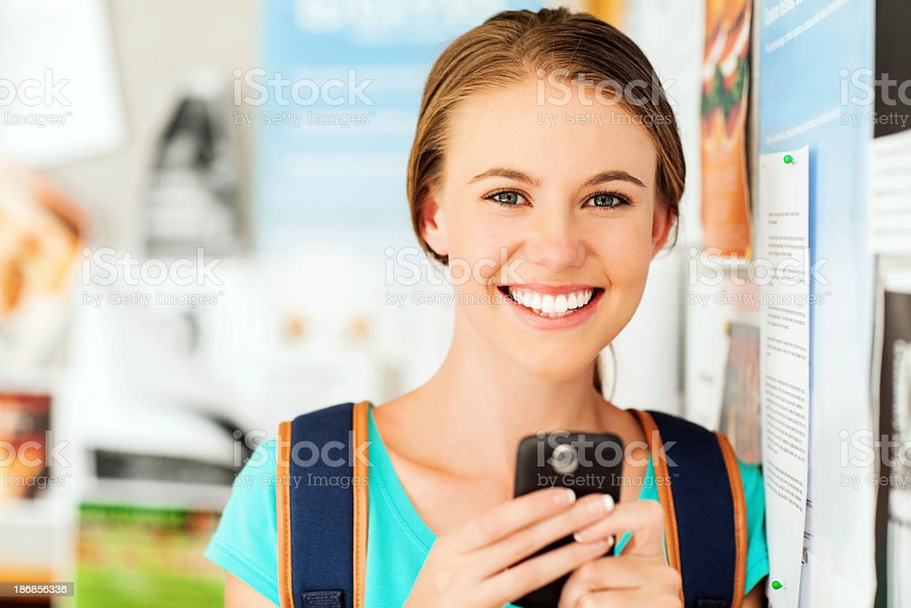 Girl Using Smart Phone While Leaning On Bulletin Board royalty-free stock photo