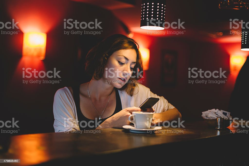 Girl using smartphone in a cafe stock photo