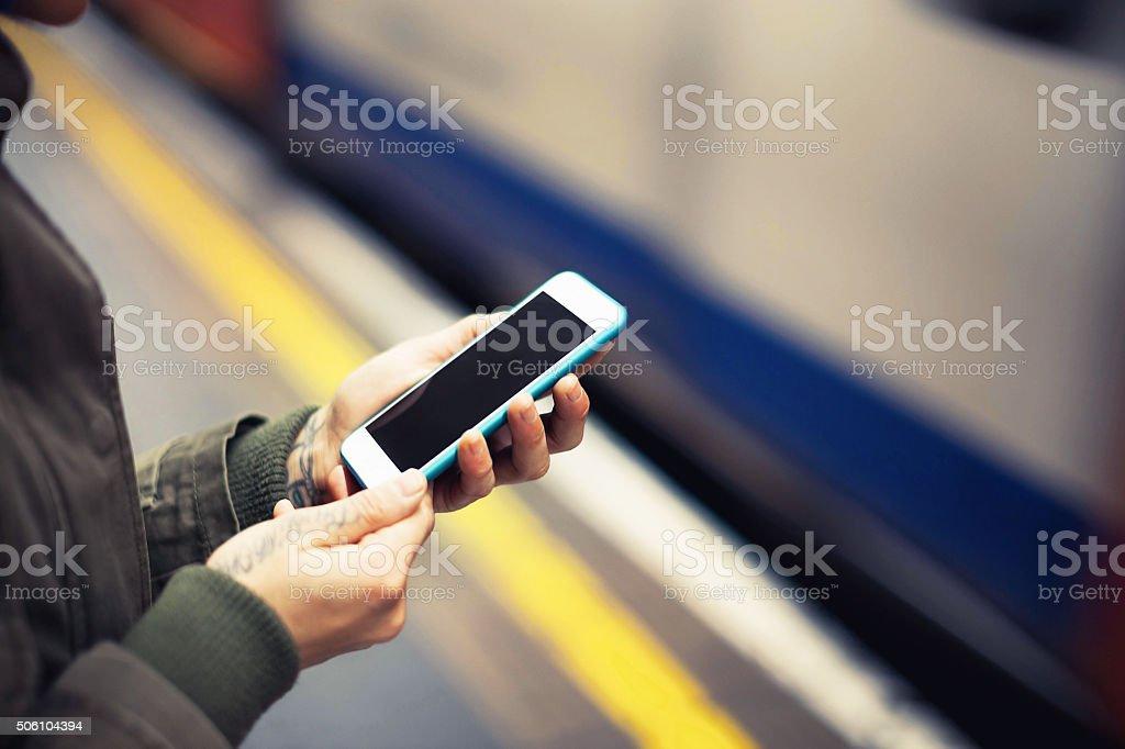 Girl using smartphone waiting the train stock photo