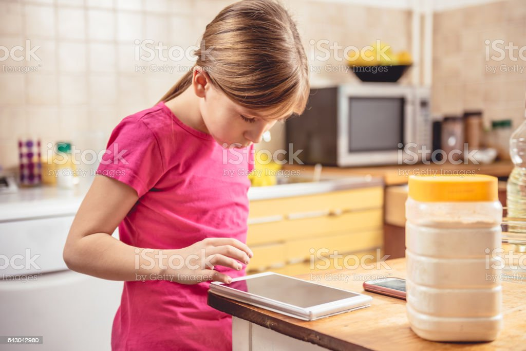 Girl using tablet in kitchen stock photo