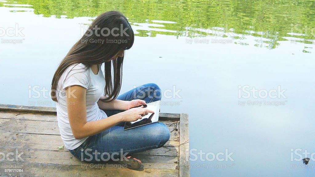 Girl using tablet pc and relaxes by the lake sitting foto de stock libre de derechos