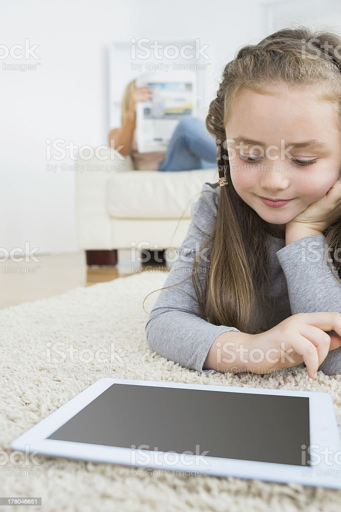 Girl using tablet with her mother reading the newspaper royalty-free stock photo