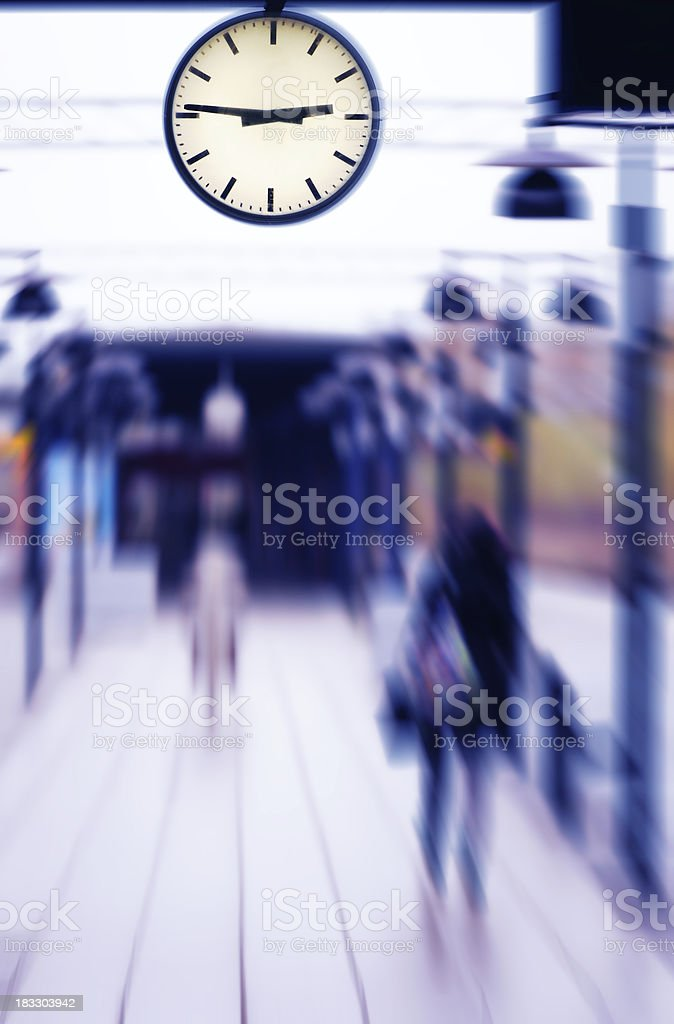 Girl waiting for train on platform. Clock close up. royalty-free stock photo