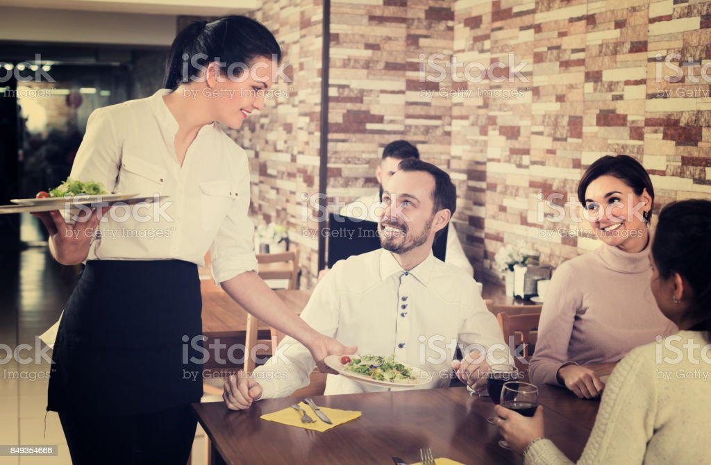 Girl waitress serving meal for restaurant guests stock photo