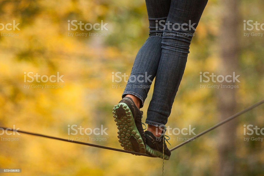 Girl walking along a tightrope stock photo