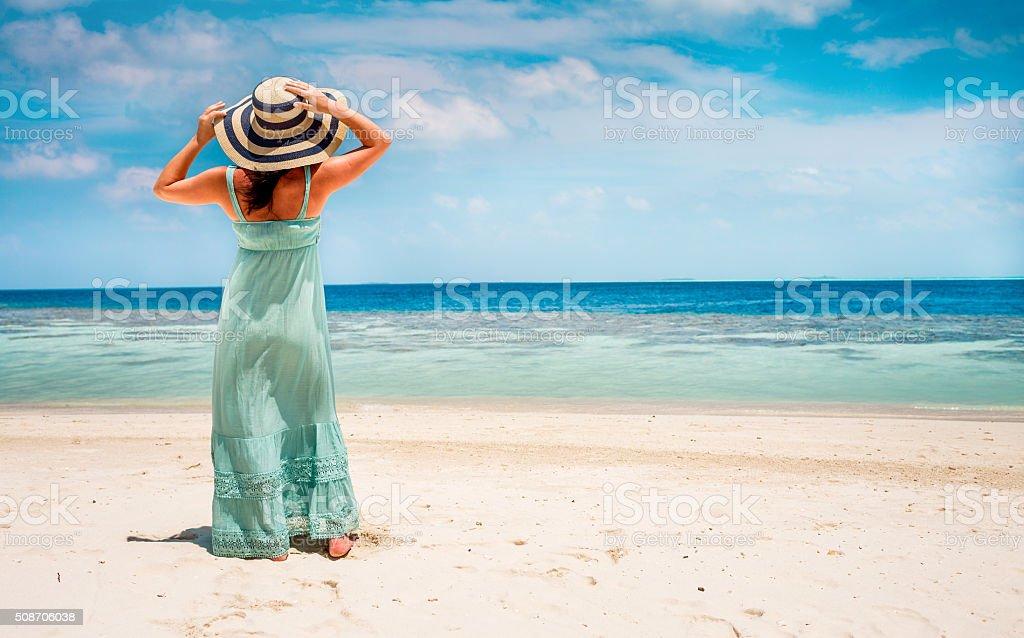 Girl walking along a tropical beach in the Maldives. stock photo