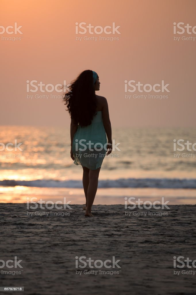 A girl walking along the beach at sunset stock photo