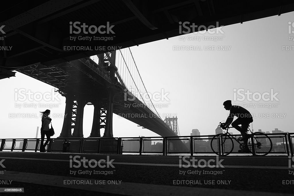 NYC girl walking and cyclist cycling under Manhattan Bridge stock photo