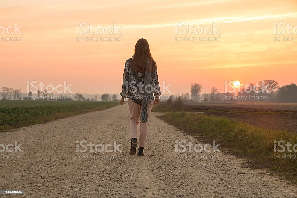 Girl walking at the sunset stock photo