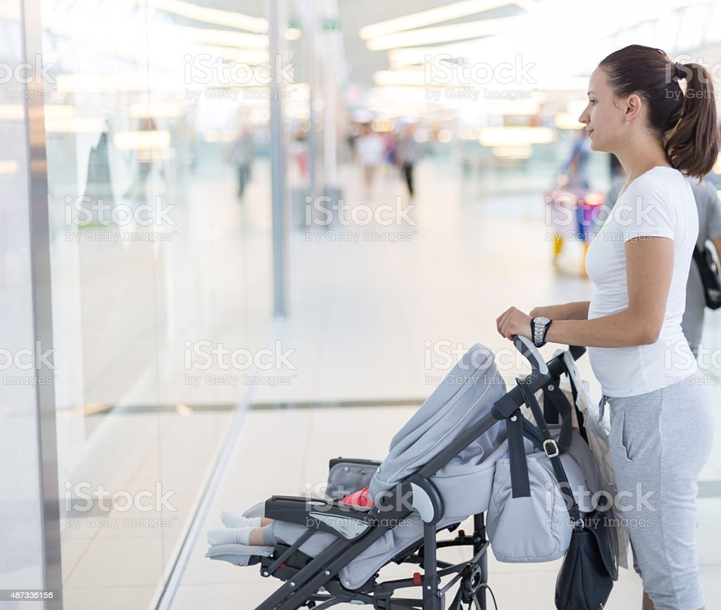 girl walking baby in baby carriage stock photo