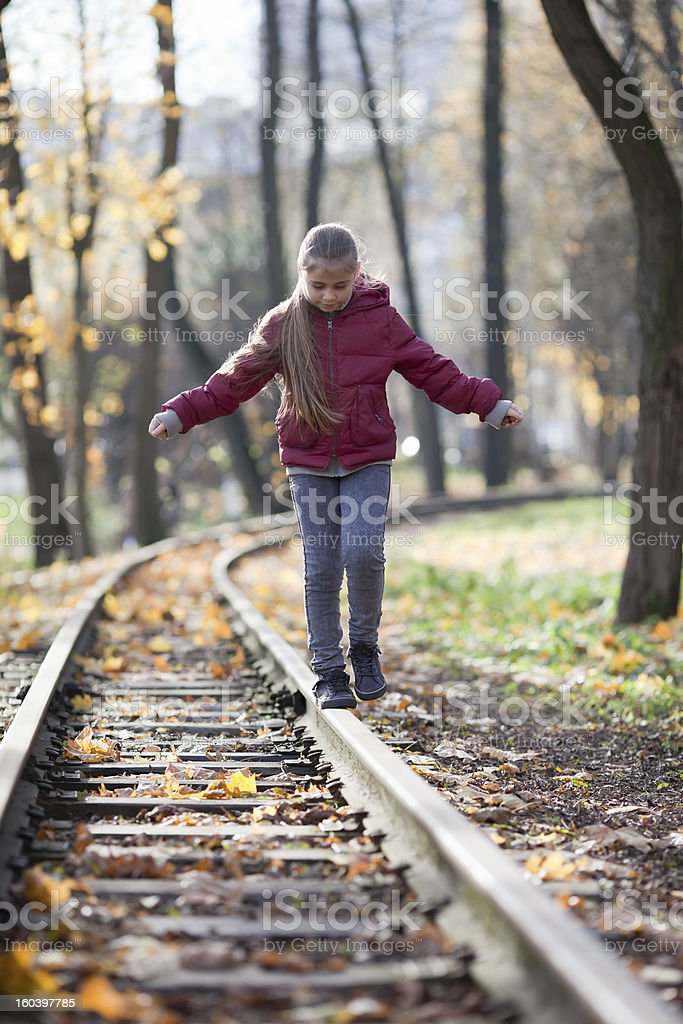 Girl walking down train tracks royalty-free stock photo