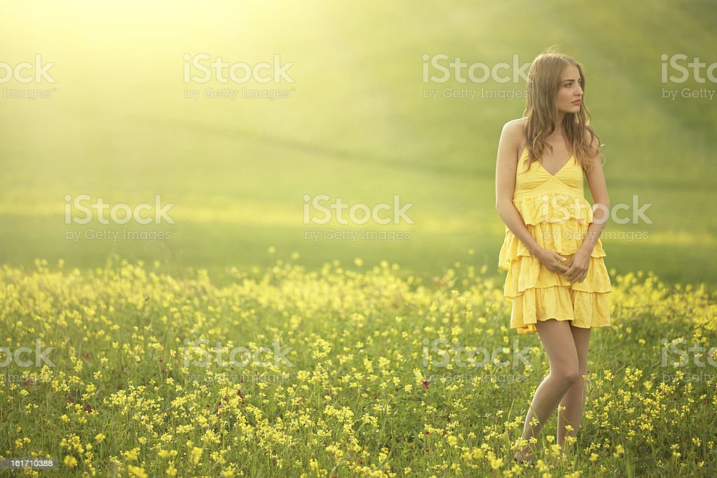 girl walking in a flower covered field royalty-free stock photo
