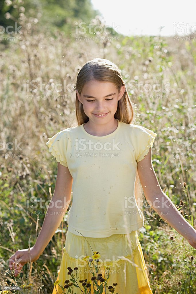 Girl walking in an overgrown field stock photo