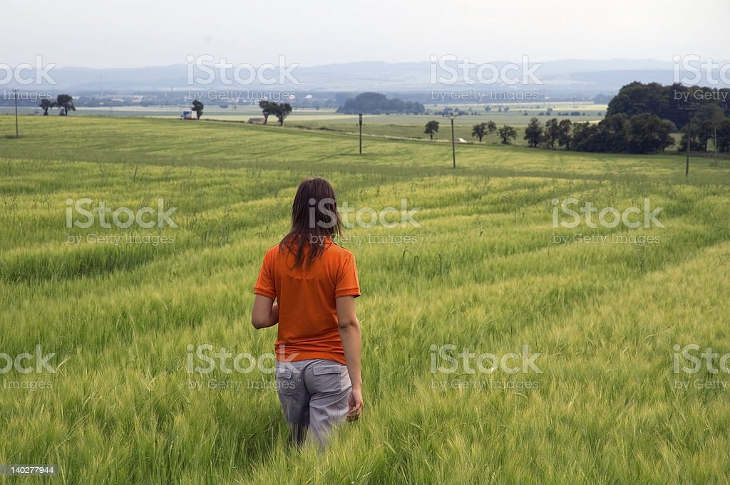 Girl walking in field overlooking valley royalty-free stock photo