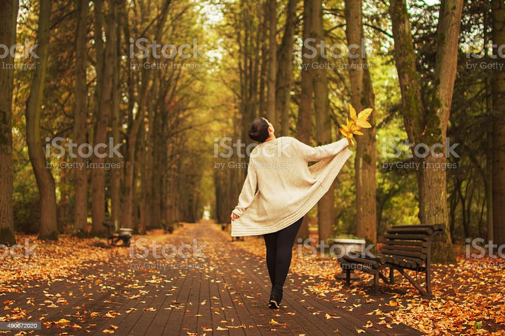 girl walking in the park in autumn stock photo