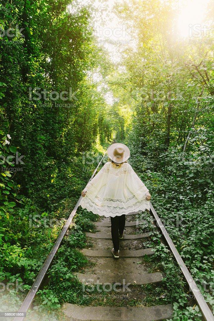 Girl walking in tree tunnel stock photo