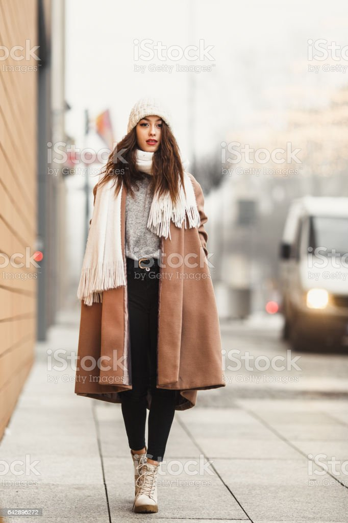 Girl walking near the wall and looking at camera. Blur yellow background stock photo