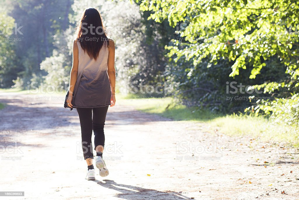 girl walking on forest trail stock photo