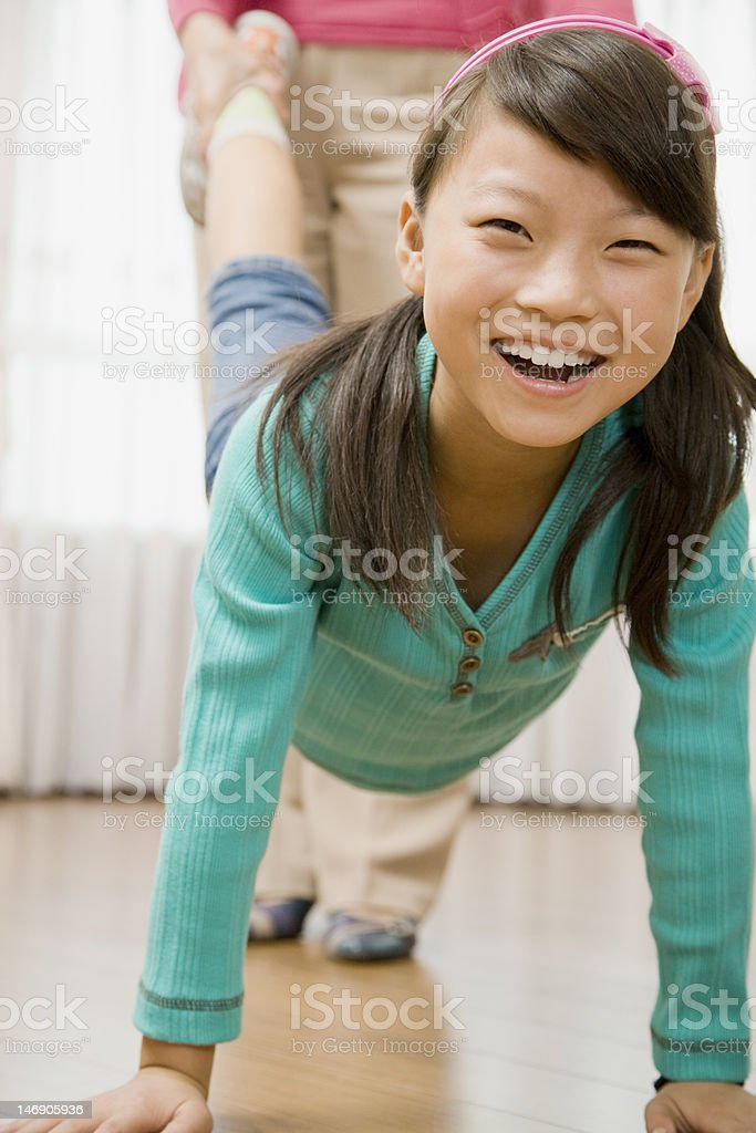 Girl Walking on Hands as Woman Holds Her Legs stock photo