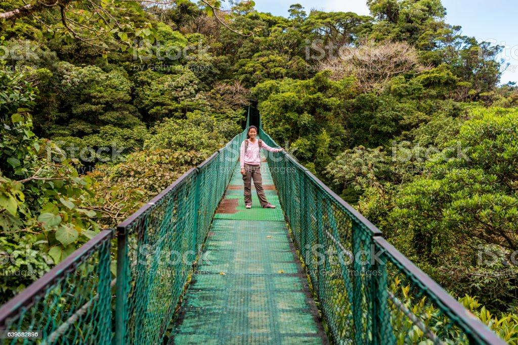Girl walking on hanging bridge in cloudforest - Monteverde stock photo