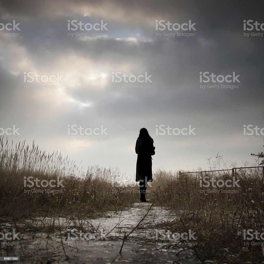 Girl walking on ice in the field stock photo