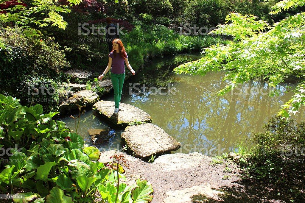Girl walking on stepping stones across pond in Japanese garden royalty-free stock photo