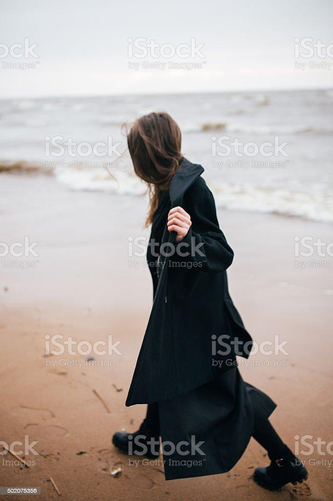 Chica caminando por la orilla del mar foto de stock libre de derechos