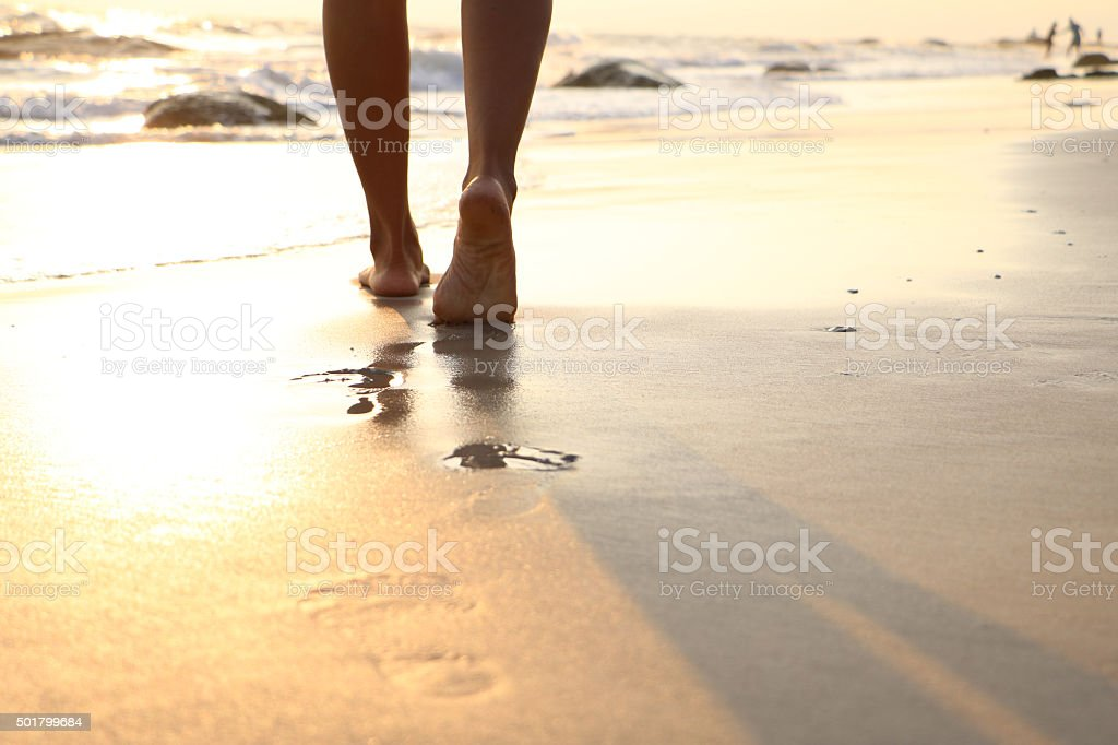 Girl walking on wet sandy beach leaving footprints in the sand at...