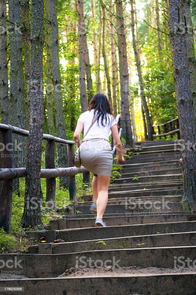 Girl walking through the forest pathway royalty-free stock photo