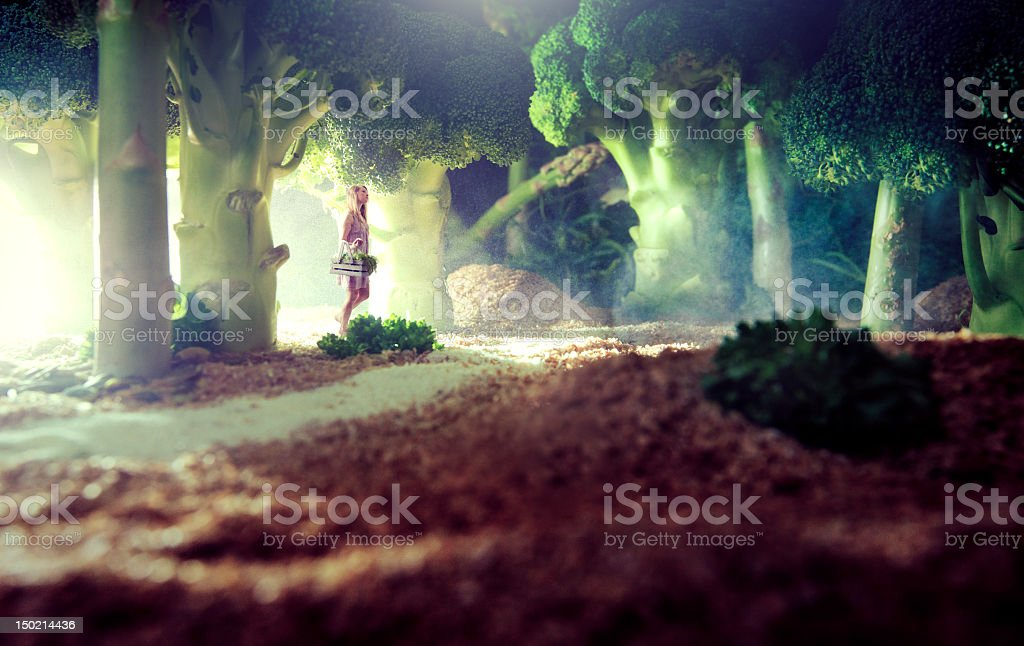 Girl walking through trees of broccoli and asparagus stock photo