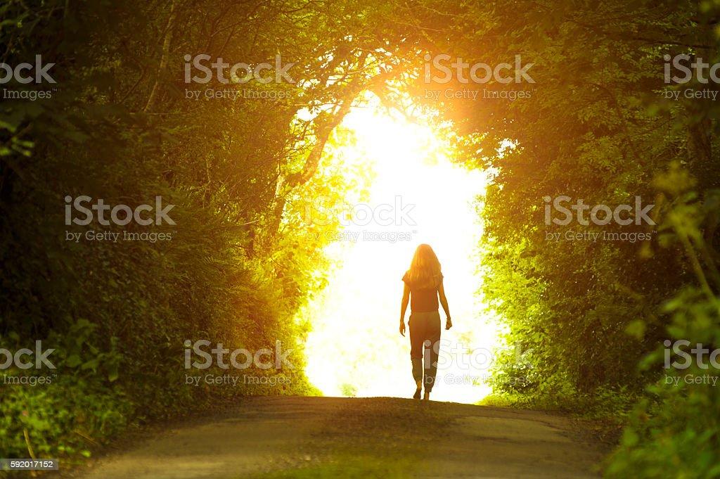 Girl walking towards the light stock photo