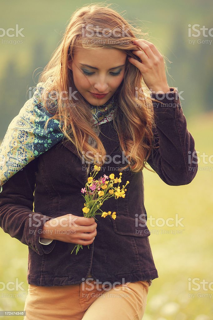 girl walking with a boquet of wild flowers royalty-free stock photo