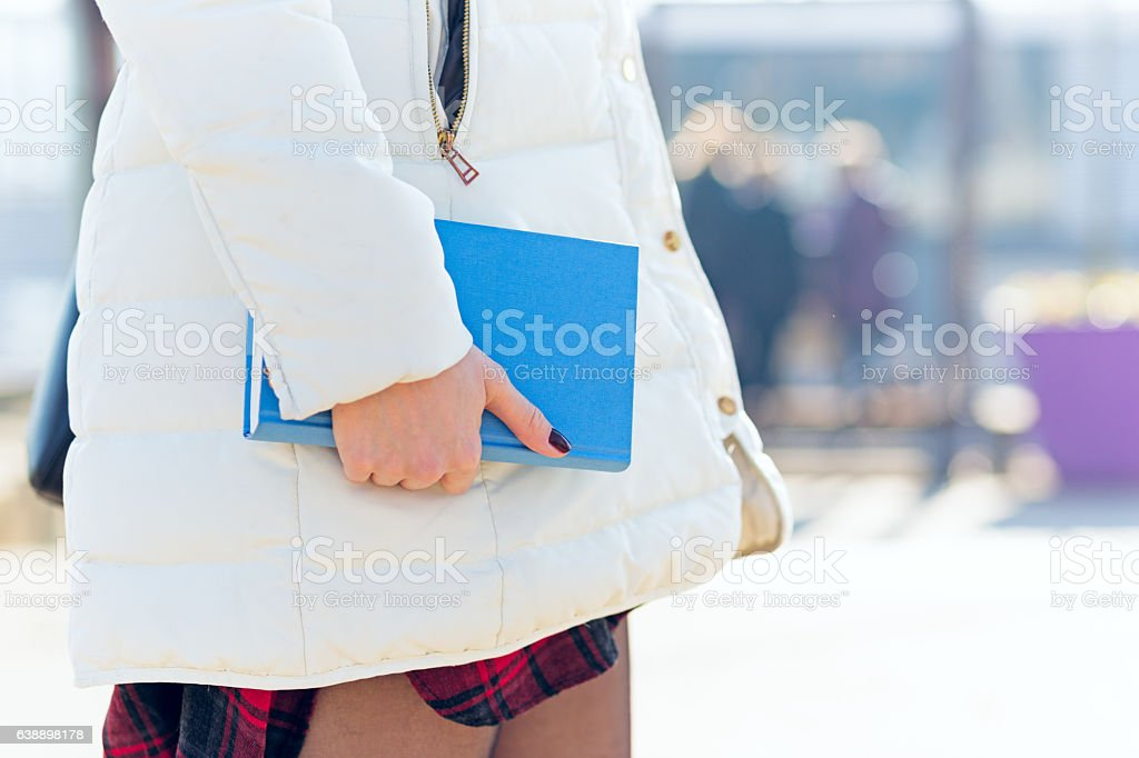 Girl walking with blue book in her hand stock photo