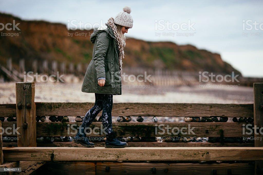 Girl walks along groyne stock photo