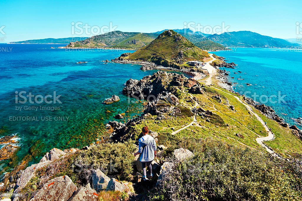 Girl walks down from Genoese Tower of Parata peninsula stock photo