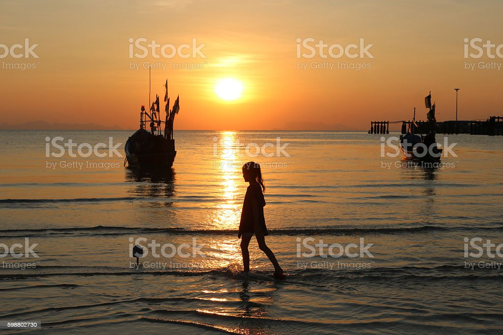 Girl walks on the beach and fishing boats. stock photo