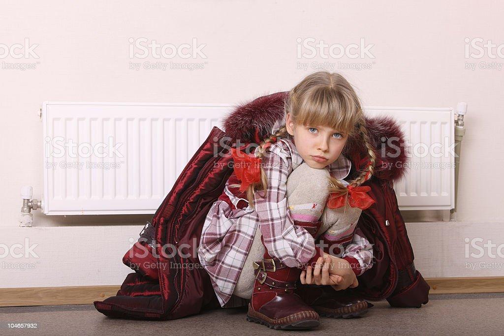Girl warm near radiator. Energy crisis. royalty-free stock photo