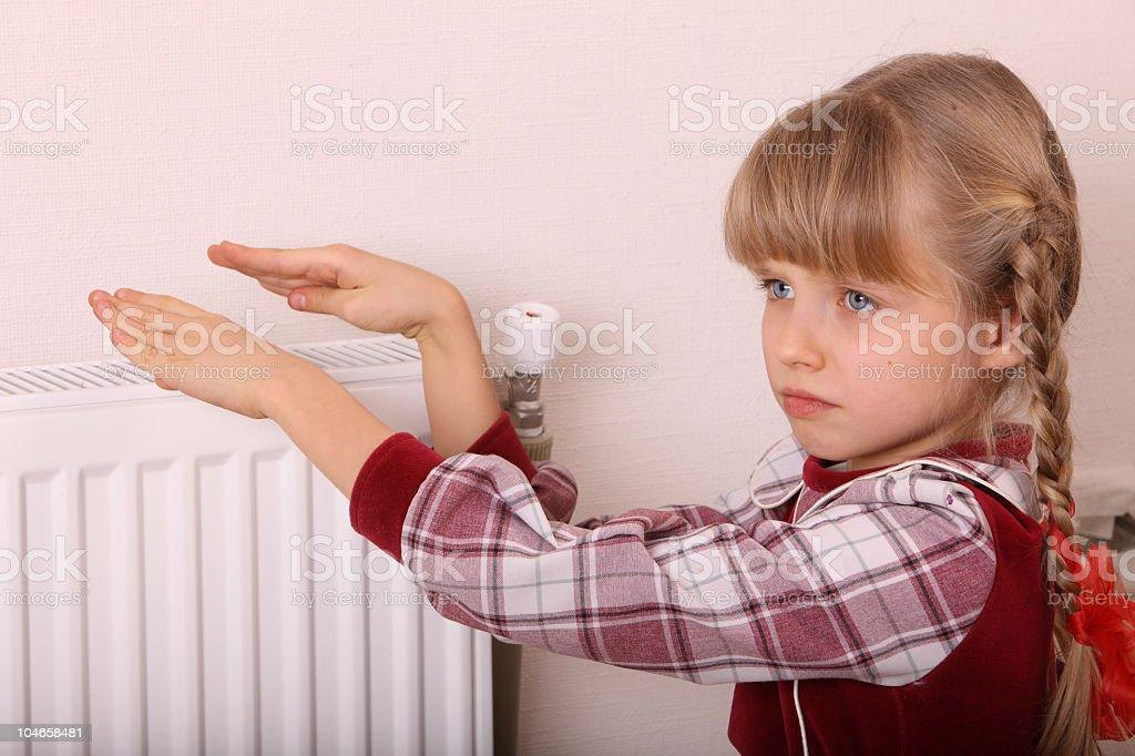 Girl warming her hands near the heat radiator royalty-free stock photo