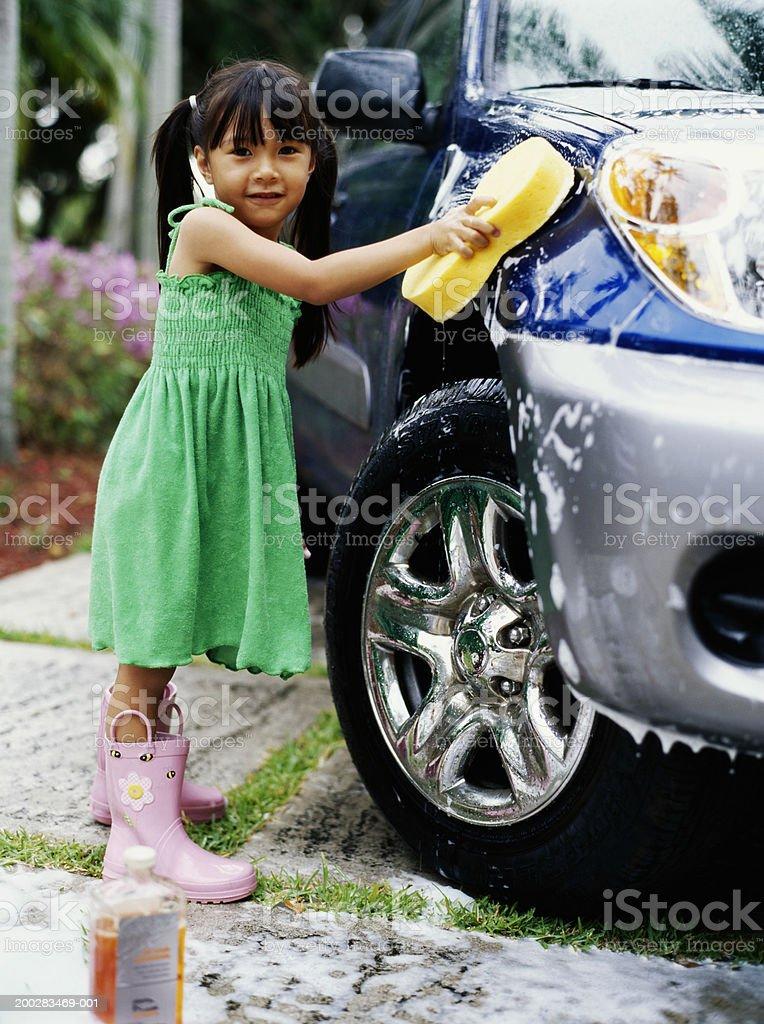 Girl (4-6) washing car in driveway, smiling, portrait stock photo
