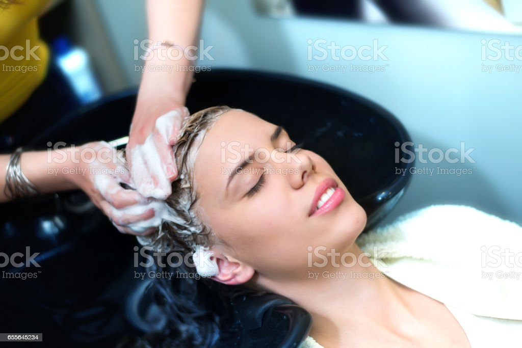 Girl washing hair in hairdressing salon stock photo